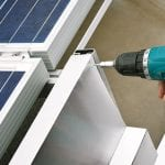 Worker with power drill installing windbreaker on solar panel construction - Downer EDI optimised
